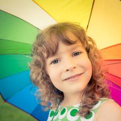 Happy child against multicolor umbrella background