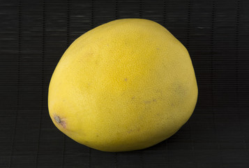 Yellow pomelo on a black background