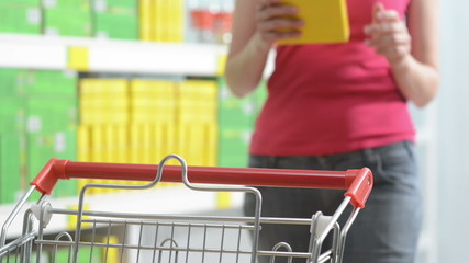 Young woman taking products from store shelves at supermarket wi