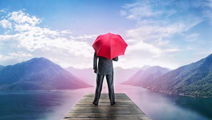Man with umbrella standing on te pier