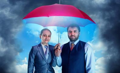 Business couple under umbrella