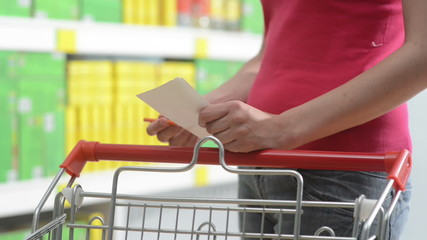 Young woman shopping with trolley at supermarket and checking a