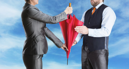 Businesswoman gives umbrella to businessman
