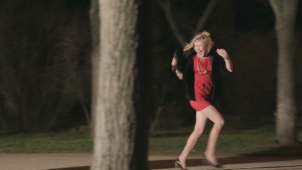 Beautiful girl runs away from maniac through the dark park