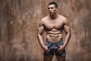 Muscular man posing in jeans shorts on wall background