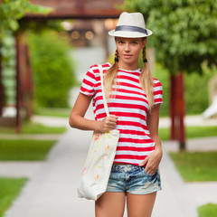 Beautiful sexy female in shorts and striped t-shirt, in hat
