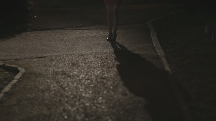 Shadow and the girl's legs in high heels standing in the dark