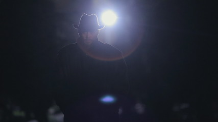 Mysterious man in a black cloak and hat standing at night in the