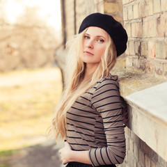 portrait of a beautiful young girl in a beret in a sunny day