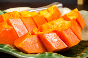 Arrange fresh yellow papaya on green leaf dish on wooden backgro
