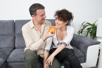 Couple sit on grey couch together eating
