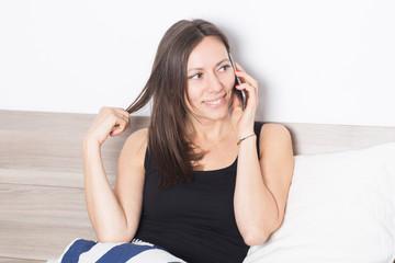 Frau telefoniert im Bett