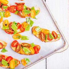 Spring Bruschetta with tomatoes and young green peas