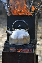 the whistling kettle begins to boil on a brazier