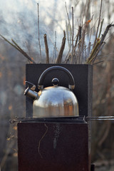 the whistling kettle begins to boil on a brazier.