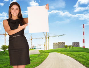 Young woman holding blank poster with industry on background