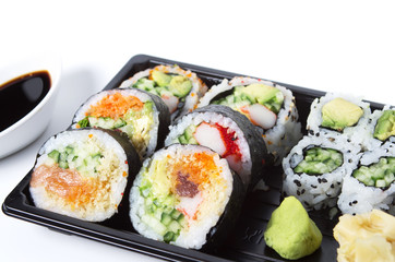 Assorted sushi rolls in a black plastic tray against white backg