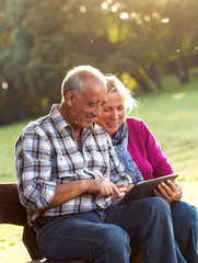 Senior couple sitting on a park bench looking at tablet