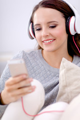 Young beautiful woman at home sitting on sofa and listening