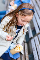 Little girl eating outdoors