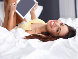 Women use a tablet pc on the bed
