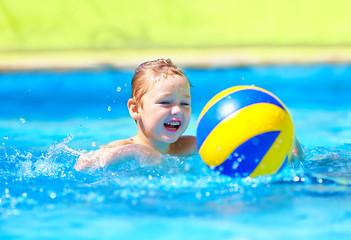 cute kid playing in water sport games in pool