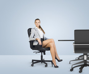 Businesslady sitting half-turned in chair with her crossed legs
