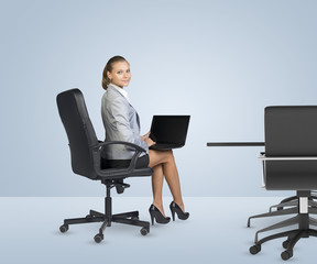 Rear view of businesslady sitting at table, holding laptop