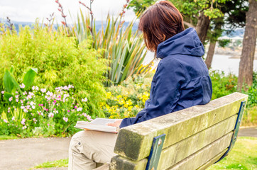 Young Woman Reading a Book in a Park