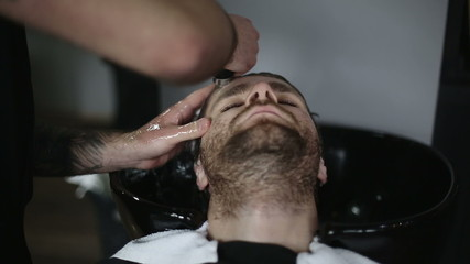 Man Barber Washing Male Hair in a Barbershop