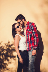 Young fashion elegant stylish couple posing on streets