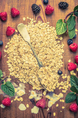 oat flakes pile with spoon and fresh berries on wooden