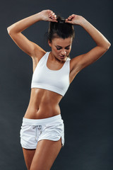 Attractive athletic young woman posing in studio on dark backgro