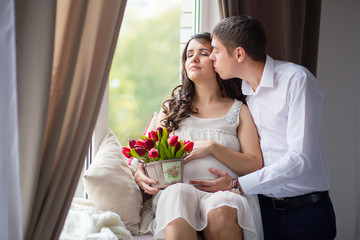 young pregnant woman with husband sitting on the window and kiss
