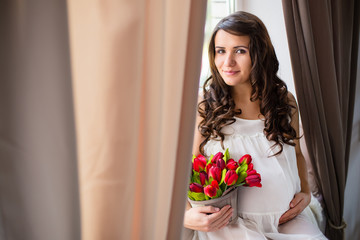 young pregnant woman sit on window with flowers