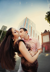 Young couple hug and kiss in city centre