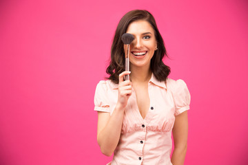 Happy young woman covering her eyes with brush