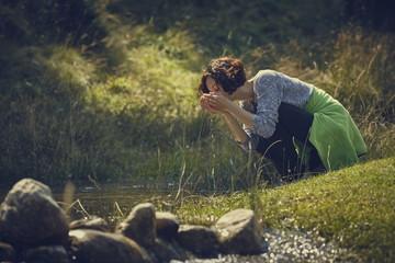 Woman drinking creek fresh water
