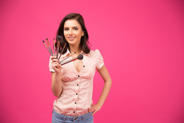 Smiling young woman holding brushes