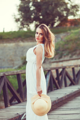 Beautiful young woman in an elegant white dress with a hat in he