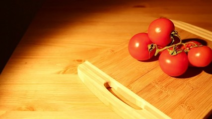 A bunch of tomatoes on a cutting board from a sliding dolly
