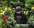 Leinwanddruck Bild - The fountain surrounded by flowers