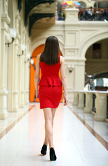 Young woman in red dress walking in the shop