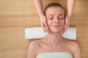 Beautiful young woman getting relaxing head massage. Top view
