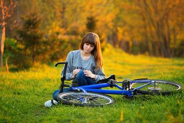 Woman with pain in knee joints after biking on bicycle in park a