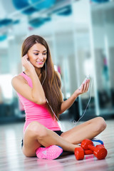Smiling athletic woman sit and training with earphones in a fitn