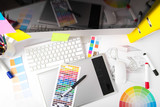 Modern office workplace with digital tablet, notepad, colorful p