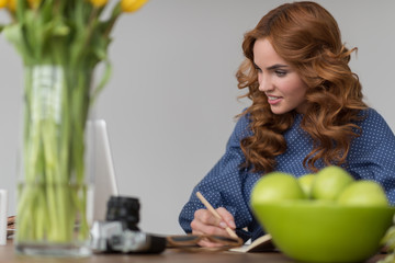 Woman writing something in diary or notepad