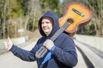 Man with guitar on shoulder try to stop car