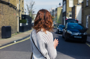 Woman walking in street with parked cars